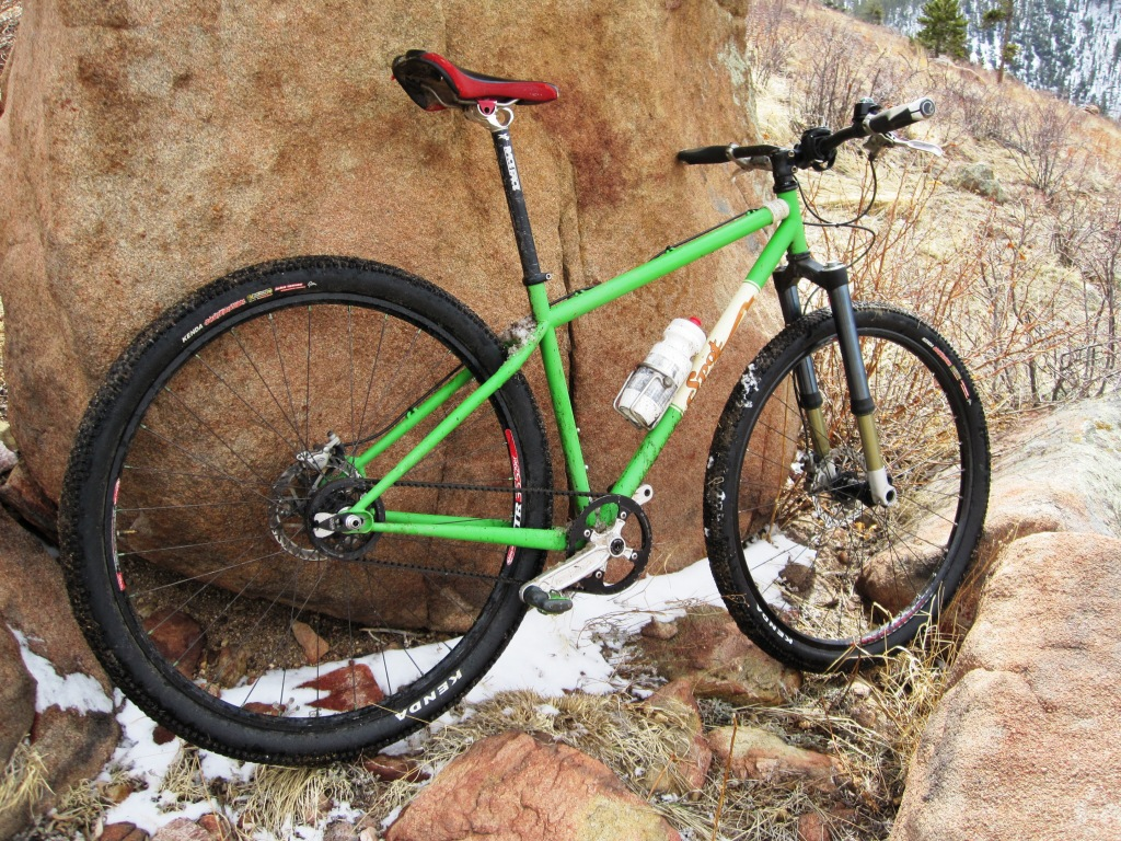 green carbon drive belt bike against rock