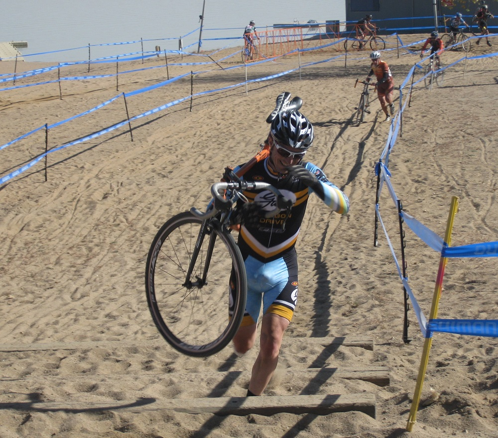 Cross racer climbing steps carrying his bicycle equipped with Gates Carbon Drive belt system