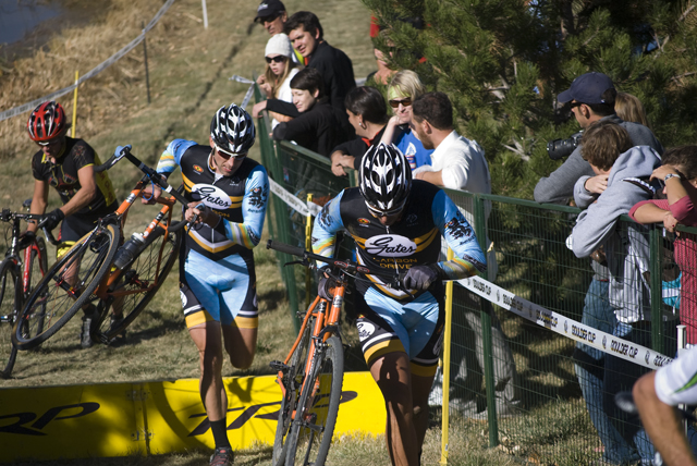 fans watching cross racers climb steps carrying their bikes