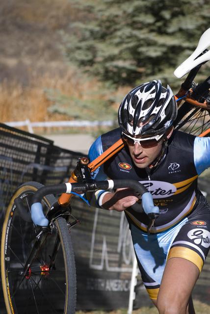 cross racing carrying his bike