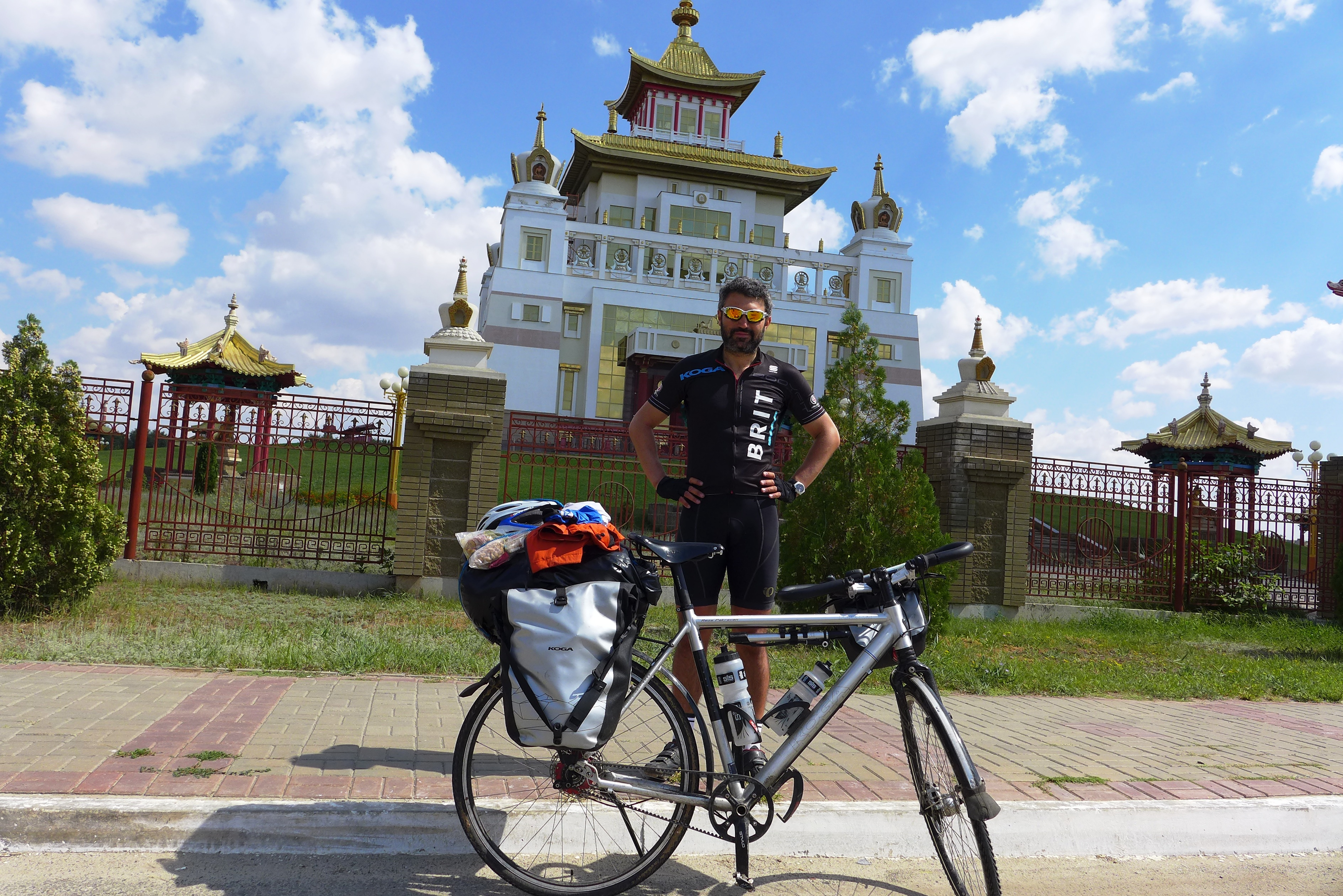 Reza standing with bike in front of temple