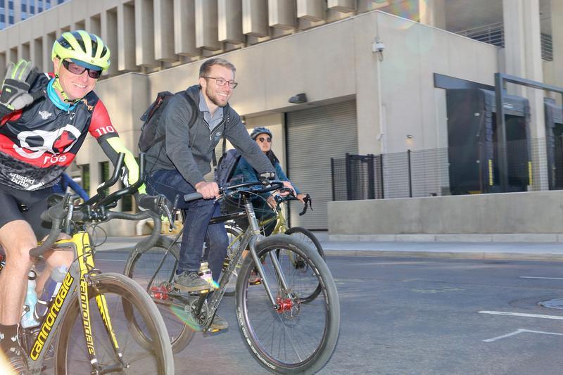 Two men riding two bikes