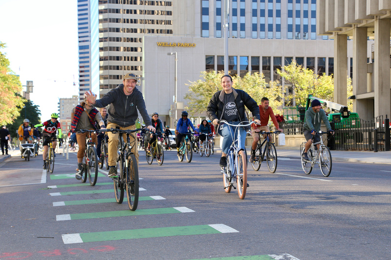 Two riders in focus while other bikers ride behind them down the streets of Denver