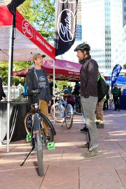 Two men discuss a belt drive bicycle
